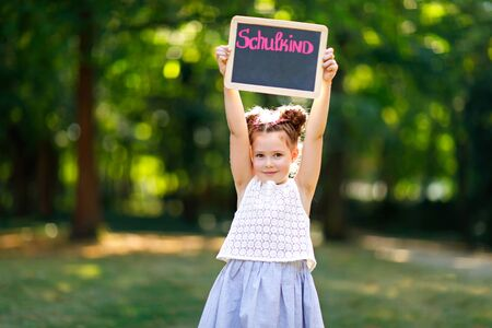 Happy little kid girl standing with desk and backpack or satchel. Schoolkid on first day of elementary class. Healthy adorable child outdoors, in green park. On desk - Schoolchild - in German Stock Photo
