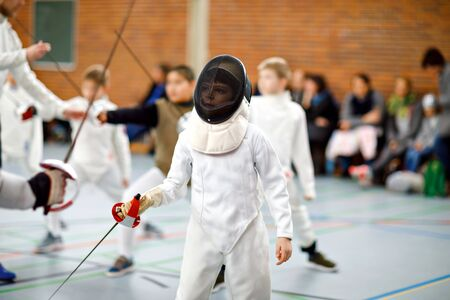 Little kid boy fencing on a fence competition. Child in white fencer uniform with mask and sabre. Active kid training with teacher and children. Healthy sports and leisure. Stok Fotoğraf