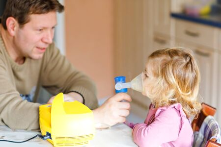 Little toddler girl making inhalation with nebulizer at home. Father helping and holding the device. Child having flu, cough and bronchitis. asthma inhaler inhalation steam sick concept