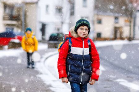 Little school kid boy of elementary class walking to school during snowfall. Happy child and student with eye glasses backpack in colorful winter clothes. schoolkid in yellow jacket on background