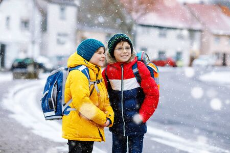 Two little kids boys of elementary class walking to school during snowfall. Happy children having fun and playing with first snow. Siblings and best friends with backpack in colorful winter clothes.