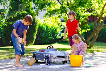 Three happy children washing big old toy car in summer garden, outdoors. Two boys and little toddler girl cleaning car with soap and water, having fun with splashing and playing with sponge.