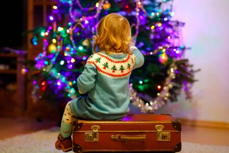 Adorable toddler girl sitting near Christmas tree. Little child playing and decorating xmas tree with family. First celebration. Surprised toddler and colorful lights on background.