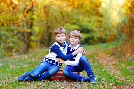 Portrait of little school kids boys sitting in forest. Happy children, best friends and siblings having fun on warm sunny day early autumn. Twins and family, nature and active leisure.