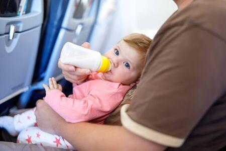 Vater hält seine kleine Tochter während des Fluges im Flugzeug in den Ferien