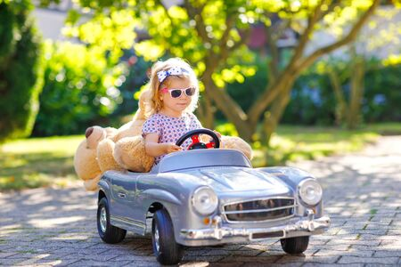 Kleines entzückendes Kleinkindmädchen, das große Oldtimer-Spielzeugautos fährt und Spaß beim Spielen mit Plüschspielzeugbären im Freien hat. Herrliches glückliches gesundes Kind, das warmen Sommertag genießt. Lächelndes atemberaubendes Kind im Gaden Standard-Bild