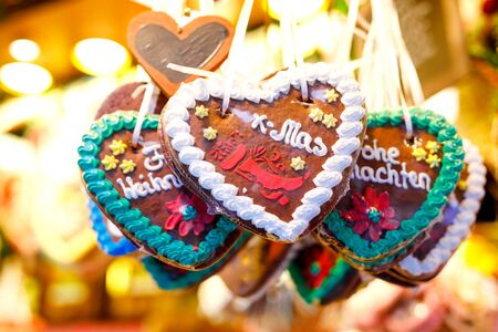Gingerbread Hearts at German Christmas Market. Nuremberg, Munich, Fulda, Berlin, Hamburg xmas market in Germany. In German language Merry Christmas. 스톡 콘텐츠