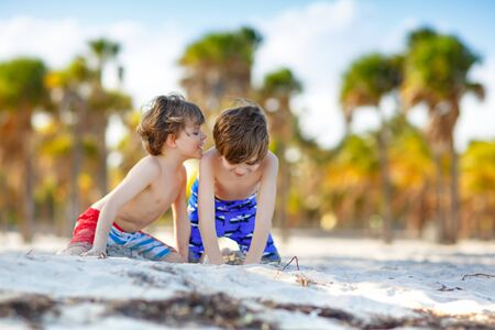 Two little kids boys having fun on tropical beach, happy best friends playing with sand, friendship concept. Siblings brothes in swim trousers. Key Biscayne, Miami, Florida