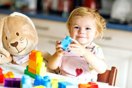 Adorable toddler girl with favorite plush bunny playing with educational toys in nursery. Happy healthy child having fun with colorful different plastic blocks at home. Cute baby learning creating.