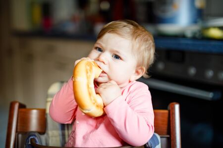 Cute little baby girl eating bread. Adorable child eating for the first time piece of pretzel or croissant. Healthy smiling happy child. First teeth coming. At home indoors in the kitchen.