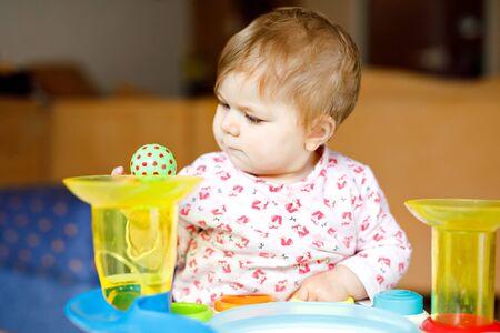 Adorable linda y hermosa niña jugando con juguetes educativos en casa o en la guardería. Niño sano feliz divirtiéndose y clasificando diferentes bolas de plástico de colores. Niño aprendiendo diferentes habilidades. Foto de archivo