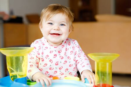 Adorable cute beautiful little baby girl playing with educational toys at home or nursery. Happy healthy child having fun and sorting colorful different plastic balls. Kid learning different skills