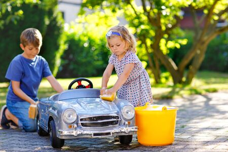 Two happy children washing big old toy car in summer garden, outdoors. Brother boy and little sister toddler girl cleaning car with soap and water, having fun with splashing and playing with sponge. Stock Photo