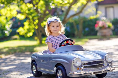Little adorable toddler girl driving big vintage toy car and having fun with playing outdoors. Gorgeous happy healthy child enjoying warm summer day. Smiling stunning kid playing in domestic garden