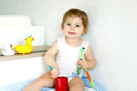 Little baby girl holding toothbrush and brushing first teeth. Toddler learning to clean milk tooth.