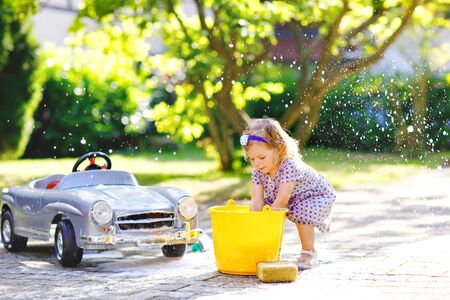 Cute gorgeous toddler girl washing big old toy car in summer garden, outdoors. Happy healthy little child cleaning car with soap and water, having fun with splashing and playing with sponge.