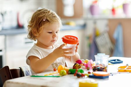 Adorable cute little toddler girl with colorful clay. Healthy baby playing and creating toys from play dough. Small kid molding modeling clay and learning Foto de archivo