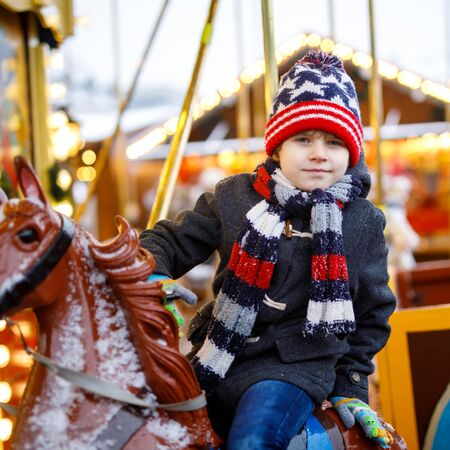 Adorable little kid boy riding on a merry go round carousel horse at Christmas funfair or market, outdoors. Happy child having fun on traditional family xmas market in Hamburg, Germany.