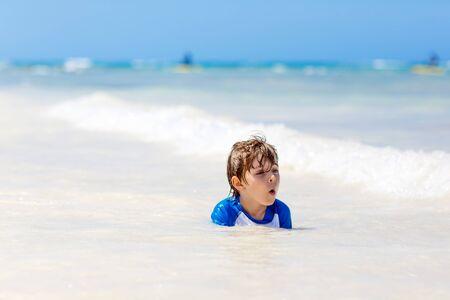 little blond kid boy having fun on tropical beach of Mexiko Stock Photo