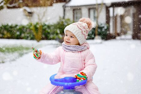 Cute little toddler girl enjoying a sleigh ride on snow. Child sledding. Baby kid riding a sledge in colorful fashion clothes. Outdoor active fun for family winter vacation on day with snowfall Stok Fotoğraf