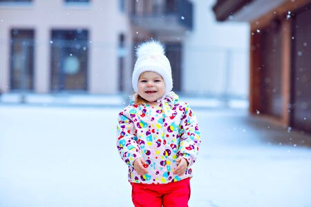 Portrait of little toddler girl walking outdoors in winter. Cute toddler eating sweet lollypop candy. Child having fun on cold snow day. Wearing warm baby colorful clothes and hat with bobbles. Foto de archivo - 129325066