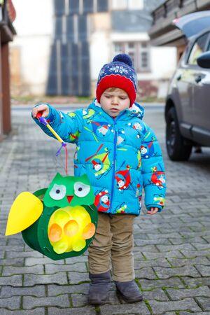 Niño niño sosteniendo linternas hechas a sí mismo para una procesión de Halloween o San Martín. Hermoso niño lindo sano feliz por los niños y el desfile familiar en el jardín de infantes. Tradición alemana Martinsumzug