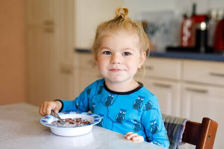 Gorgeous little toddler girl eating healthy cereal with milk for breakfast. Cute happy baby child in colorful clothes sitting in kitchen and having fun with preparing oats, cereals. Indoors at home Foto de archivo - 129325083