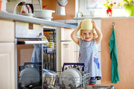 Little adorable child helping to unload dishwasher. Funny happy toddler girl standing in the kitchen, holding dishes and putting a bowl on head. Healthy kid at home Foto de archivo - 129325157