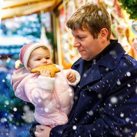 Middle aged father holding baby daughter near sweet stand with gingerbread and nuts. Happy family on Christmas market in Germany. Cute girl eating cookie called Lebkuchen. Celebration xmas holiday. Foto de archivo - 129325156