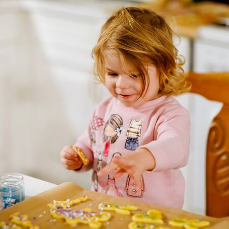 Cute little baby girl baking gingerbread Christmas cookies at home. Adorable blond child having fun in domestic kitchen. Traditional leisure with kids on Xmas. Toddler tasting dough. Foto de archivo - 129325160