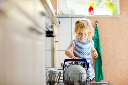 Little adorable cute toddler girl helping to unload dishwasher. Funny happy child standing in the kitchen, holding dishes and putting a bowl on head. Healthy kid at home. Gorgeous helper having fun Foto de archivo - 129325268