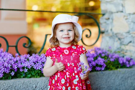Portrait of beautiful little gorgeus lovely toddler girl in pink summer look clothes, fashion dress, knee socks and hat. Happy healthy baby child posing infront of colorful house. Foto de archivo - 129325278