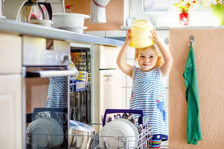 Little adorable cute toddler girl helping to unload dishwasher. Funny happy child standing in the kitchen, holding dishes and putting a bowl on head. Healthy kid at home. Gorgeous helper having fun Foto de archivo - 129325281