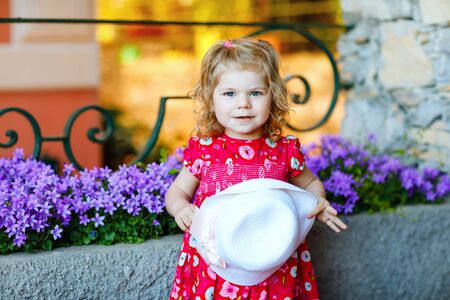 Portrait of beautiful little gorgeus lovely toddler girl in pink summer look clothes, fashion dress, knee socks and hat. Happy healthy baby child posing infront of colorful house. Foto de archivo - 129325277