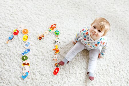 Gorgeous cute beautiful little baby girl playing with educational toys like wooden puzzle at home or nursery. Happy healthy child having fun with colorful different toys. Kid learning different skills Foto de archivo - 129325271