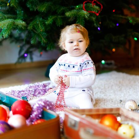 Adorable baby girl holding colorful vintage xmas toys and ball in cute hands. Little child in festive clothes decorating Christmas tree Foto de archivo - 129325287