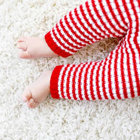Close-up of baby body and legs in red Santa Clause trousers. New born child, little girl or boy. Kid having fun. Family, new life, childhood, holiday concept. Closeup for Christmas postcard. Foto de archivo - 129325286