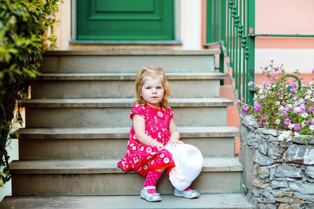 Portrait of beautiful little gorgeus lovely toddler girl in pink summer look clothes, fashion dress, knee socks and hat. Happy healthy baby child posing infront of colorful house. Foto de archivo - 129325288