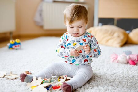 Preciosa linda y hermosa niña jugando con juguetes educativos como rompecabezas de madera en casa o en la guardería. Niño sano feliz divirtiéndose con coloridos juguetes diferentes. Niño aprendiendo diferentes habilidades.