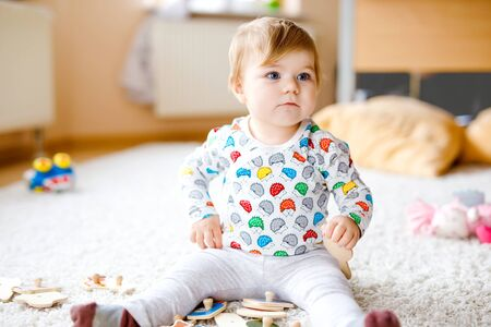 Gorgeous cute beautiful little baby girl playing with educational toys like wooden puzzle at home or nursery. Happy healthy child having fun with colorful different toys. Kid learning different skills Foto de archivo - 129325353