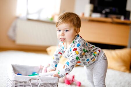 Gorgeous cute beautiful little baby girl playing with educational toys at home or nursery. Happy healthy child learning crawling and standing. Foto de archivo - 129325352