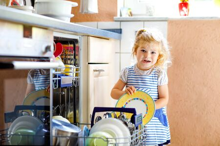 Little adorable cute toddler girl helping to unload dishwasher. Funny happy child standing in the kitchen, holding dishes and putting a bowl on head. Healthy kid at home. Gorgeous helper having fun Foto de archivo - 129325358