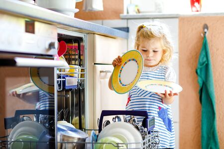 Little adorable cute toddler girl helping to unload dishwasher. Funny happy child standing in the kitchen, holding dishes and putting a bowl on head. Healthy kid at home. Gorgeous helper having fun Standard-Bild - 129325357