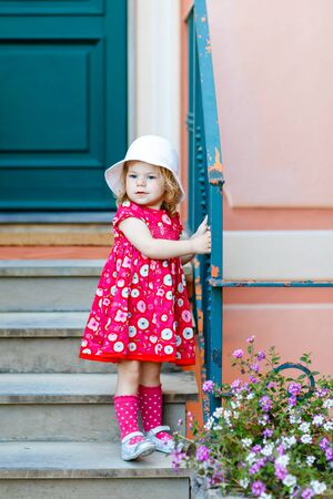 Portrait of beautiful little gorgeus lovely toddler girl in pink summer look clothes, fashion dress, knee socks and hat. Happy healthy baby child posing infront of colorful house. Foto de archivo - 129325359