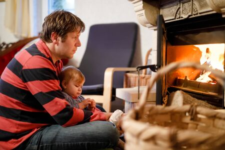 Middle age father sitting by fireplace with cute little baby girl at home. Happy family, dad with daughter make fire for Christmas time. Safe handling for kids Foto de archivo - 129325360