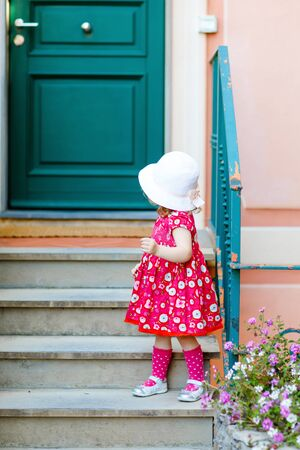 Portrait of beautiful little gorgeus lovely toddler girl in pink summer look clothes, fashion dress, knee socks and hat. Happy healthy baby child posing infront of colorful house. Foto de archivo - 129325369