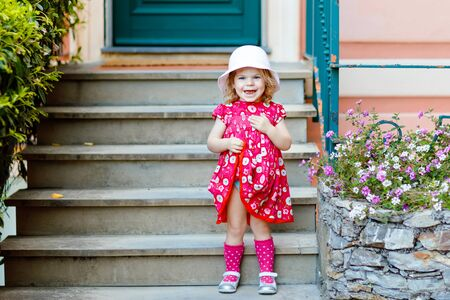 Portrait of beautiful little gorgeus lovely toddler girl in pink summer look clothes, fashion dress, knee socks and hat. Happy healthy baby child posing infront of colorful house. Foto de archivo - 129325370