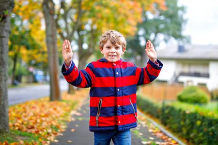Happy little boy running on autumnal street after school. Kid happy about school vacations. Child with autumn fashion clothes walking in the city. Banque d'images - 129325382