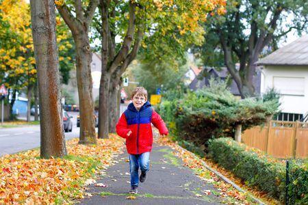 Happy little boy running on autumnal street after school. Kid happy about school vacations. Child with autumn fashion clothes wearing eye glasses Banque d'images - 129325457