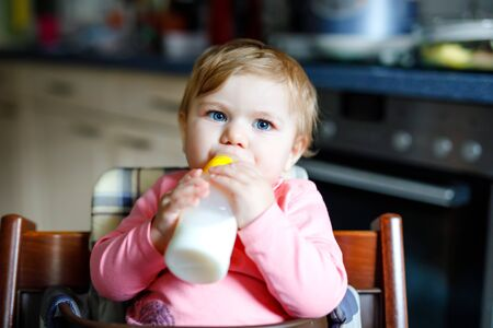 Cute adorable baby girl holding nursing bottle and drinking formula milk. First food for babies. New born child, sitting in chair of domestic kitchen. Healthy babies and bottle-feeding concept Foto de archivo - 129325450